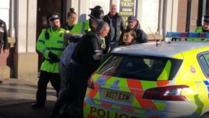 A man is in the process of being released from an angry crowd after he is disturbed by a silent tribute with fireworks at a Remembrance Sunday event at the cenotaph in Eccles