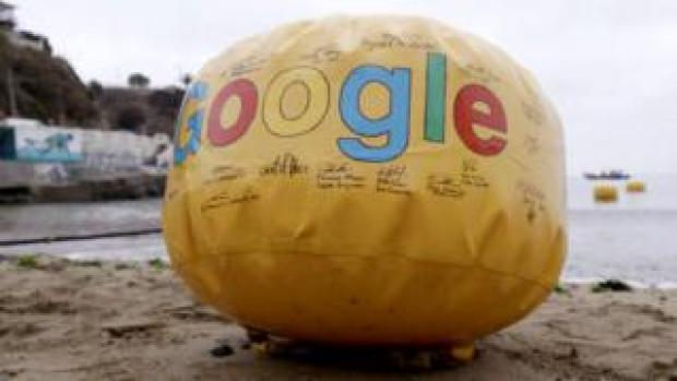 A Google-branded signed yellow buoy sits on the sand in as the first line is dropped