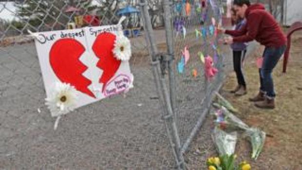 : A woman and her daughter place a heart on a fence at a growing memorial in front of the Debert School April 20, 2020