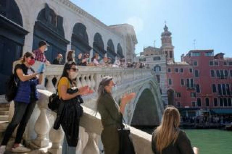 A rally of people stand on the Rialto bridge in Venice