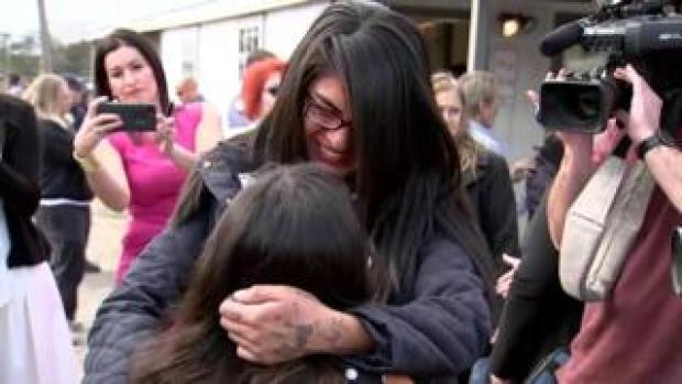 A women smiles as she hugs a young girl