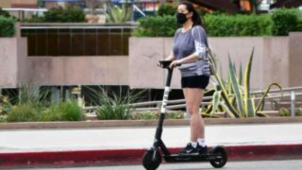 A commuter on electric scooter wears her facemask in Los Angeles on June 29, 2020