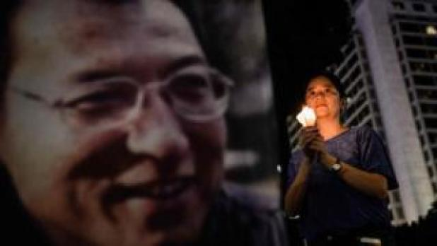 A woman holds a candle as she attends a vigil for terminally-ill Nobel laureate Liu Xiaobo (pictured on banner) in Hong Kong on June 29, 2017