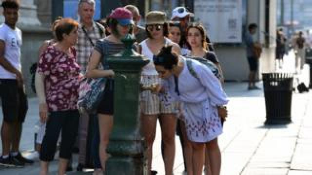 People queue to drink water from a public tap near the Duomo Cathedral, in Milan