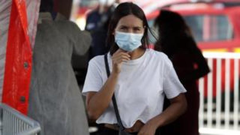 A woman wearing a protective face mask leaves after her swab samples are taken by volunteering firefighters at a test station for Covid-19 coronavirus in Marseille, France,