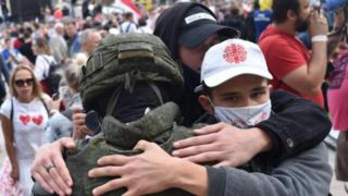 People hug a Belarus law enforcement officer during a protest rally