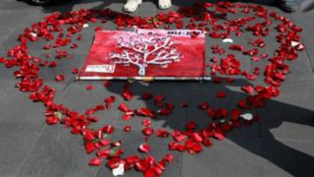 Pictures of the 43 missing students are displayed inside a heart shape made out of rose petals on the pavement in Mexico City
