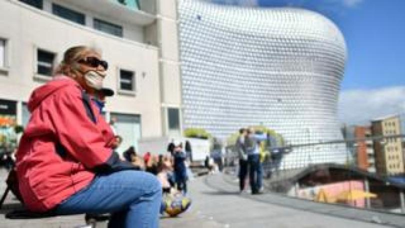 Picture of woman sitting outside the Bull Ring in Birmingham