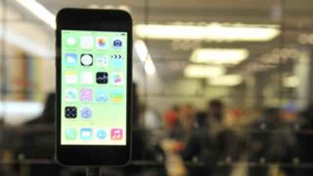 An iPhone 5 is shown in an Apple store windown display