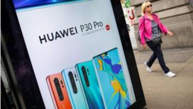 Woman walks past Huawei advert on bus stop