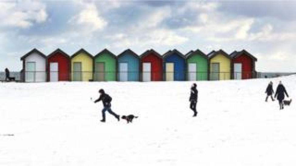 People walk their dogs in the snow on Blyth Beach in Northumberland