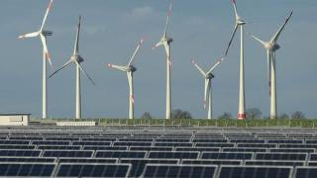 Wind turbines behind a solar power plant