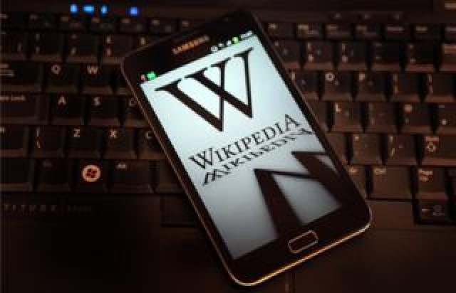 A mobile device shows Wikipedia's front page displaying a darkened logo on 18 January, 2012