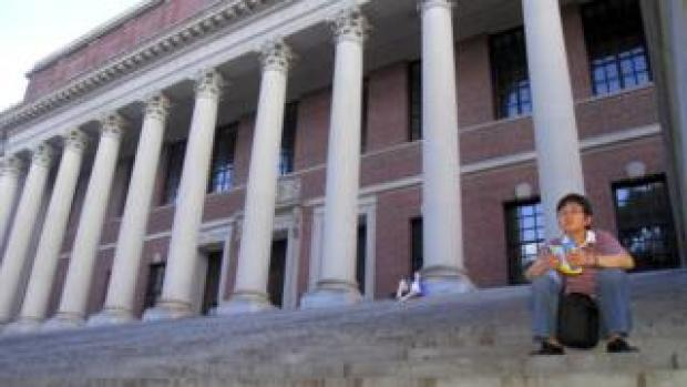 Students sit on the steps of a library at Harvard University