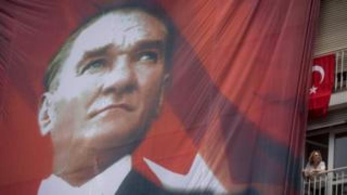 A woman watches from her balcony next to a huge banner of Mustafa Kemal Ataturk in this 2016 photo.