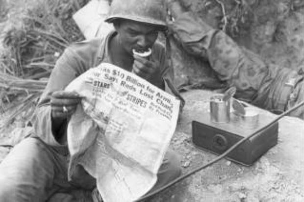 A soldier reads Star and Stripes during a lull in fighting in Korea in 1952