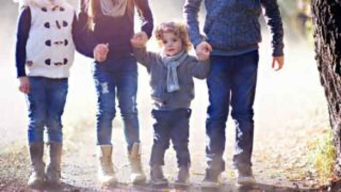 image of a little boy holding hands with his two older brothers and sisters, and a fourth child next door