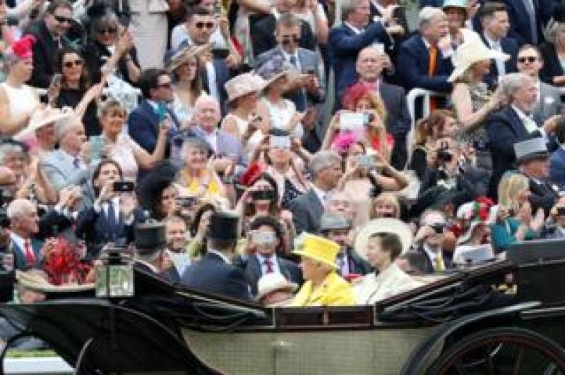 People take photos with their phones as Lord Vestey, Prince Andrew, Duke of York, Queen Elizabeth II and Princess Anne, Princess Royal arrive by carriage to Royal Ascot.