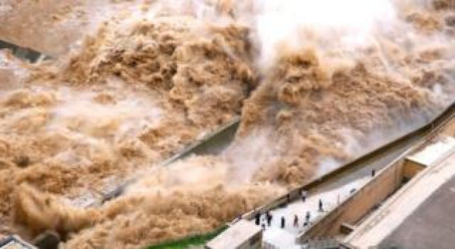 Water from a dam rushes past people