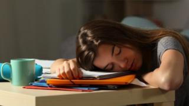 Teenager asleep at desk