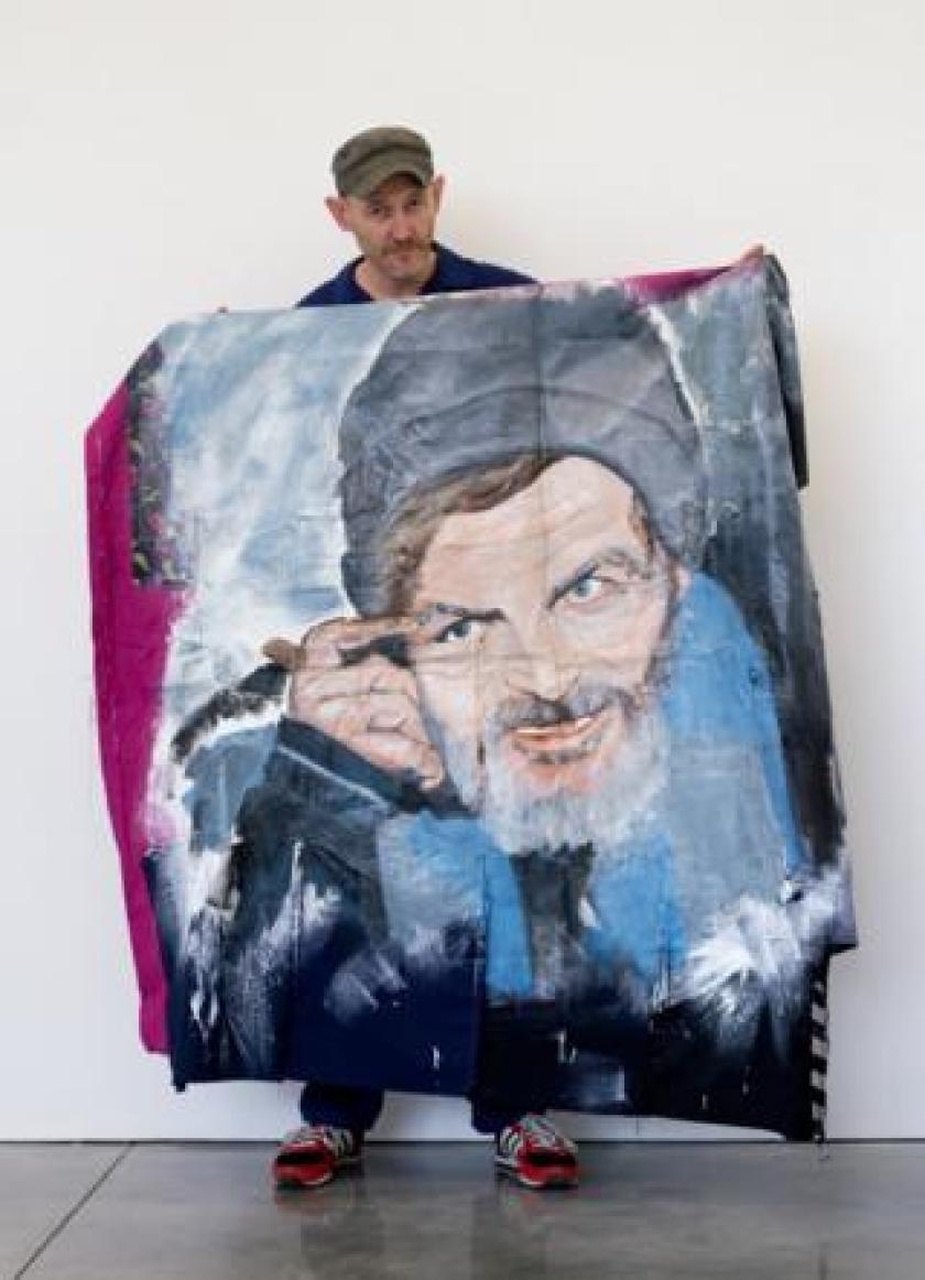 David Tovey holding his artwork