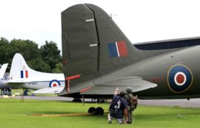 Visitors look at a vintage warplane in an open air museum