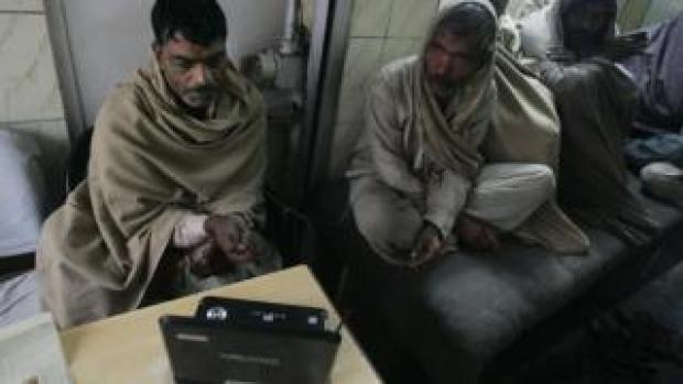 Two Indian labourers follow news on a laptop computer