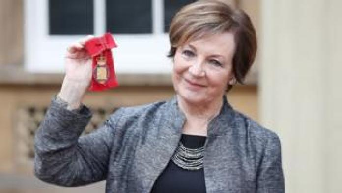 Delia Smith holding up her honour at Buckingham Palace
