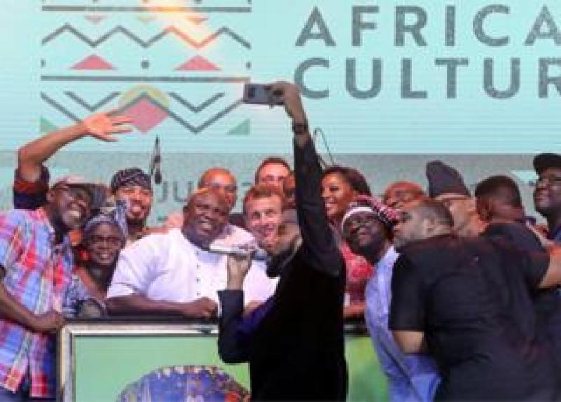 French President Emmanuel Macron (C) poses with Nigerian artists at the Afrika Shrine in Lagos, Nigeria, July 3, 2018.