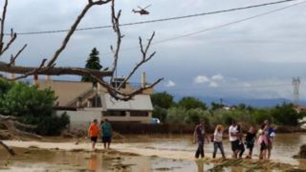 Residents leave their flooded houses after a rainstorm hit the area of Mourtzi, in Evia Island, Greece, 09 August 2020.