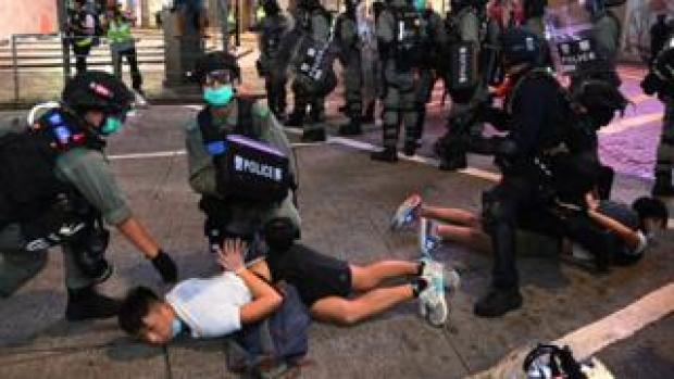 Police officers detain protesters in Hong Kong during a rally against the new national security law
