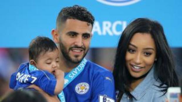 Riyad Mahrez holds daughter Inaya as wife Rita looks on