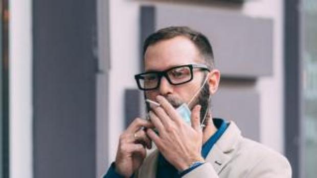 man smoking wearing mask