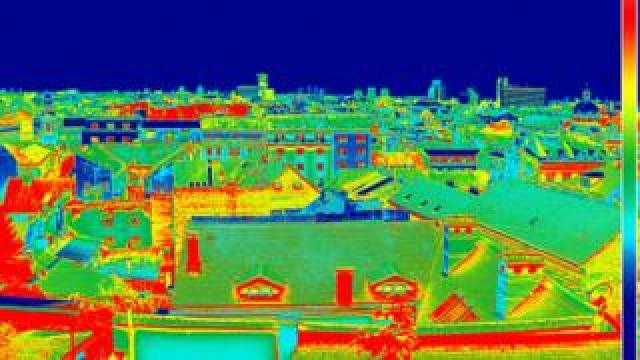 A wide shot of a housing estate seen through a thermal imaging camera.