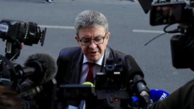 Jean-Luc Mélenchon is pictured surrounded by cameras in a press huddle on a street