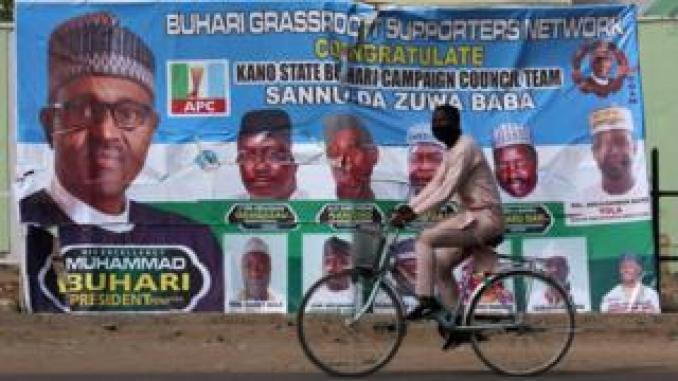 A cyclist drives pasts a campaign poster for President Muhammadu Buhari