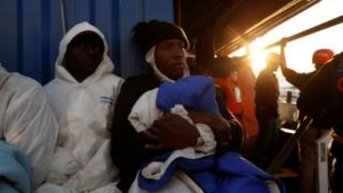 Rescued migrants rest on the migrant rescue ship