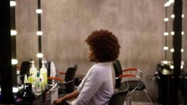 Woman sits in the mirror looking at her curly afro hairstyle