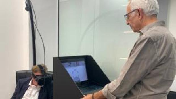 Michael Dempsey wearing headset, Dr Jamil El-Imad at computer.