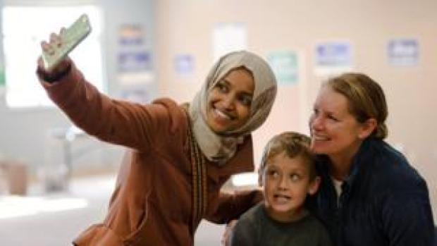 Ilhan Omar, Democratic congressional candidate, poses for a selfie with a supporter and her son while campaigning in Minneapolis, Minnesota, on October 13, 2018. -