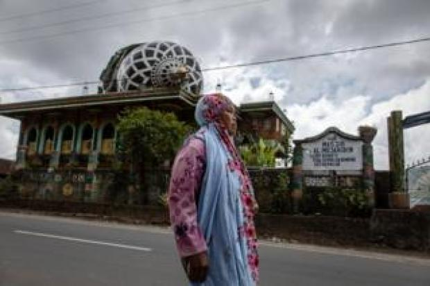 A woman walks through a collapsed mosque in Sembalun in Lombok island, Indonesia