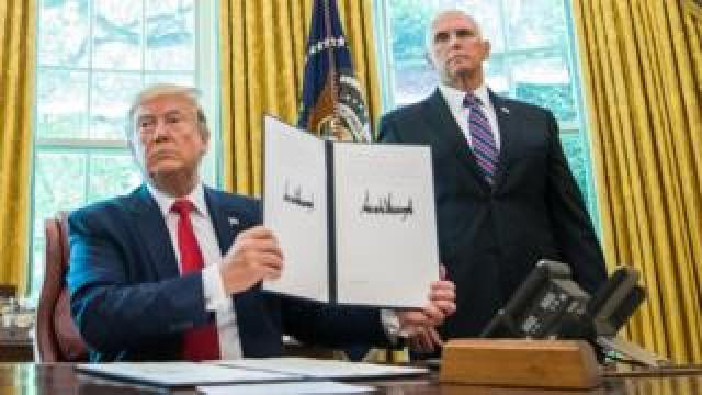 US President Donald J. Trump holds up a copy of an executive order in the Oval Office