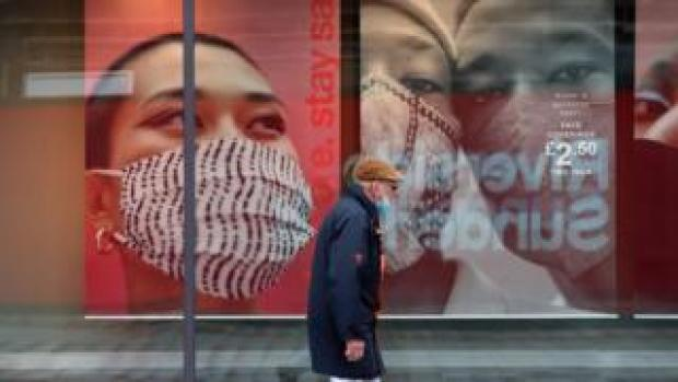 A man walks past an advertisement for face coverings in Sunderland