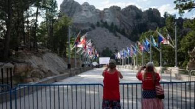 Visitors take pictures of the Mount Rushmore National Monument in Keystone, South Dakota on 2 July