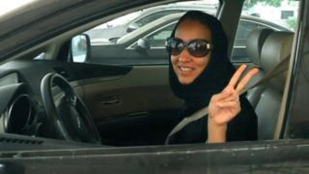 Saudi activist Manal Al Sharif flashes the sign for victory in her car on October 22, 2013
