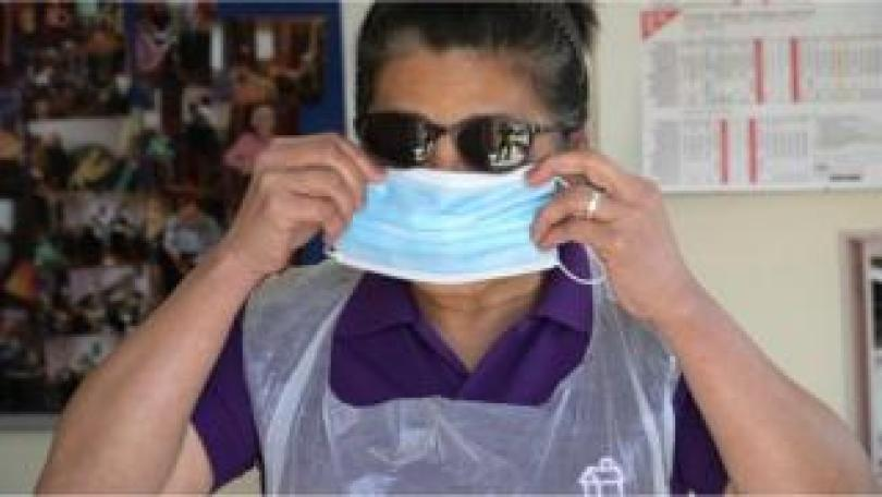 Nurse puts on personal protective equipment