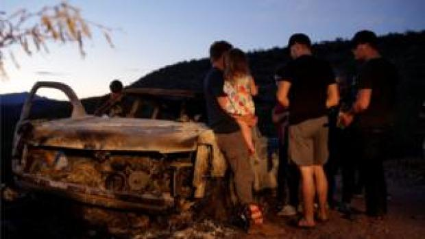 Relatives of victims look at burned vehicle