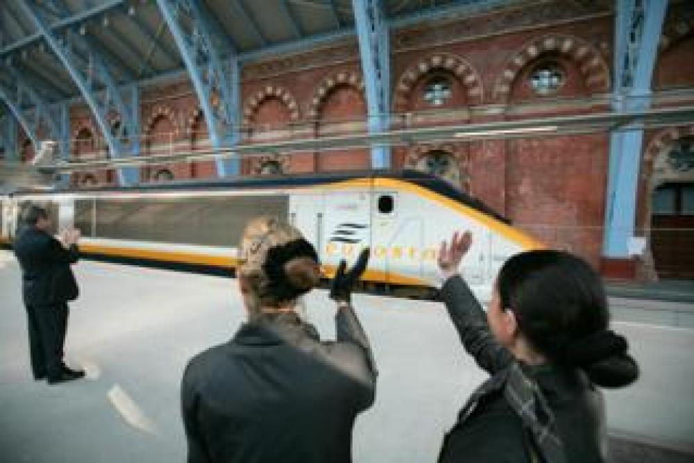 Eurostar staff wave off the first high speed train to Paris at the new terminal at St Pancras station