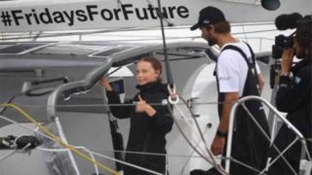 Greta Thunberg gives a thumbs up from her yacht after arriving in New York