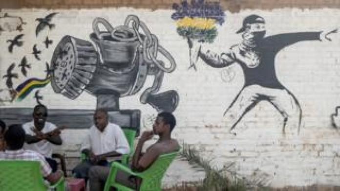 People drinking tea or coffee in front of a mural drawn in the style of Banksy - Khartoum, Sudan